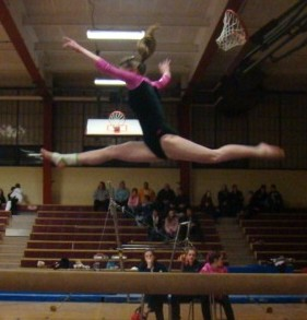 Senior Amanda Carney performs on the balance beam during a gymnastics meet.