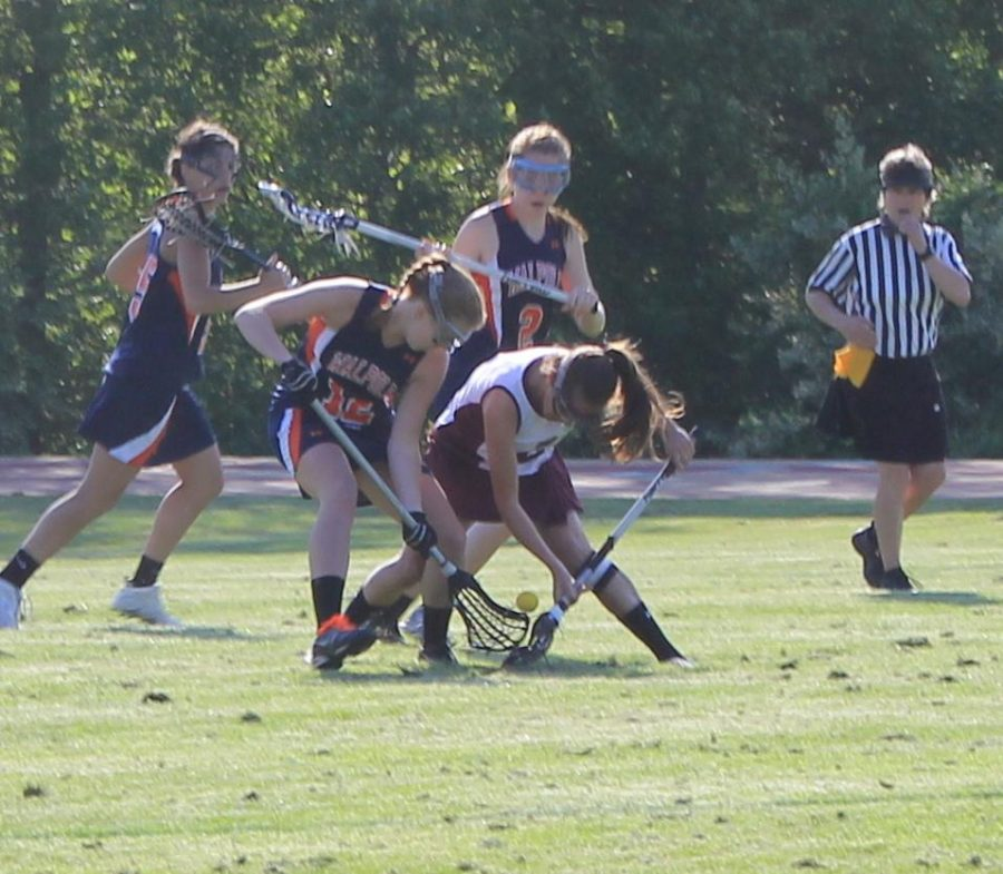 A Walpole midfielder fights for a ground ball against a Falmouth defender.