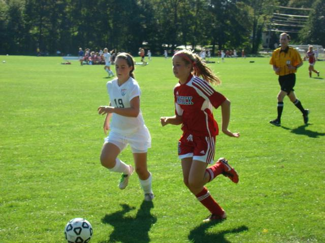 A Walpole defender follows a Natick forward down the sideline to prevent a cross.