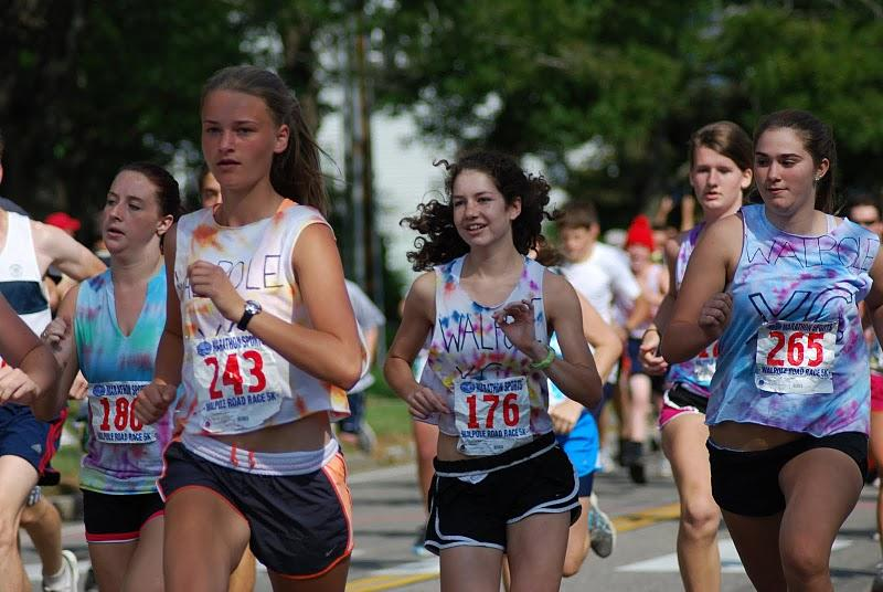 A junior Cross Country runner leads a few freshmen Cross Country runners at the beginning of the race.