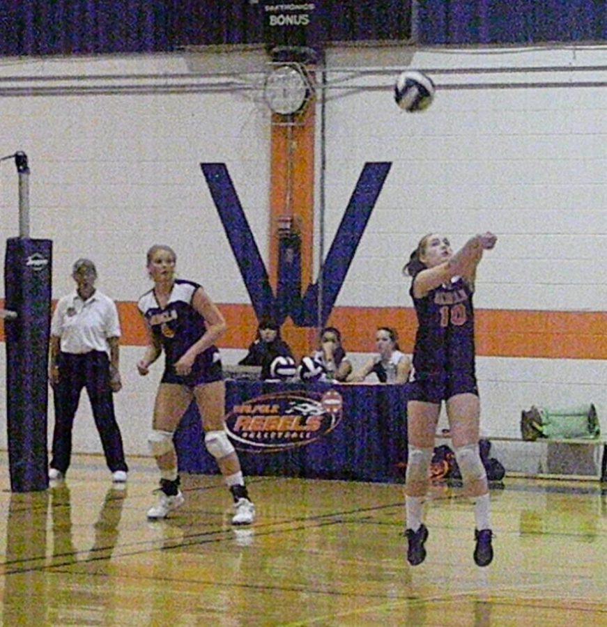 A Walpole player passes the ball while a teammate looks on.