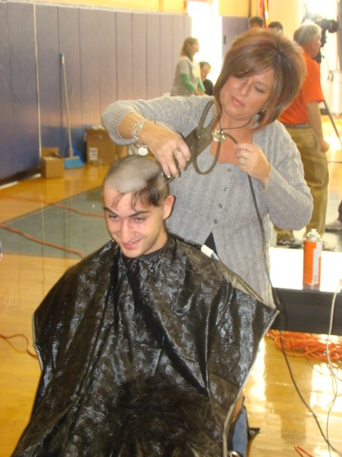 A Rebel football player shaves his head to raise money for Cancer Research.