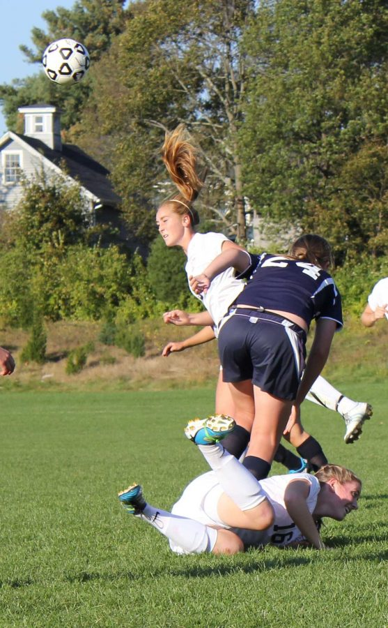 A Rebel midfielder jumps over her teammate to head the ball.