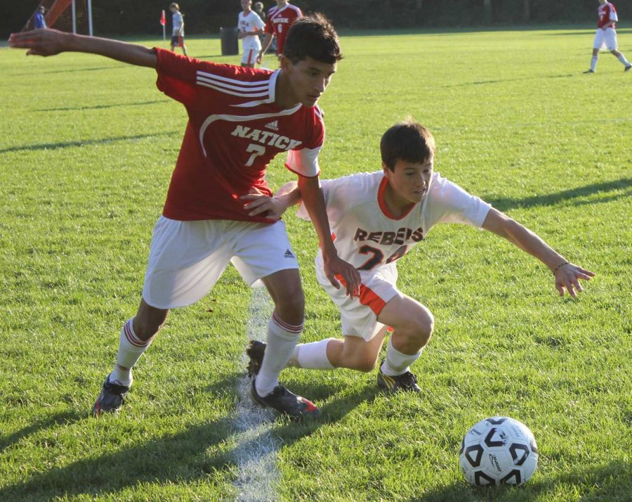 A Walpole midfielder holds off a Natick player for the ball.