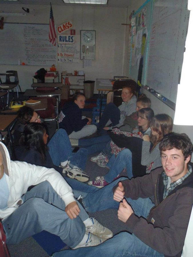 Students gather in the dark to avoid being seen or heard during the lockdown drill.