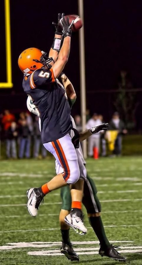 A Walpole receiver goes up and over a Dennis-Yarmouth defender. (Photo/Tim Hoffman)