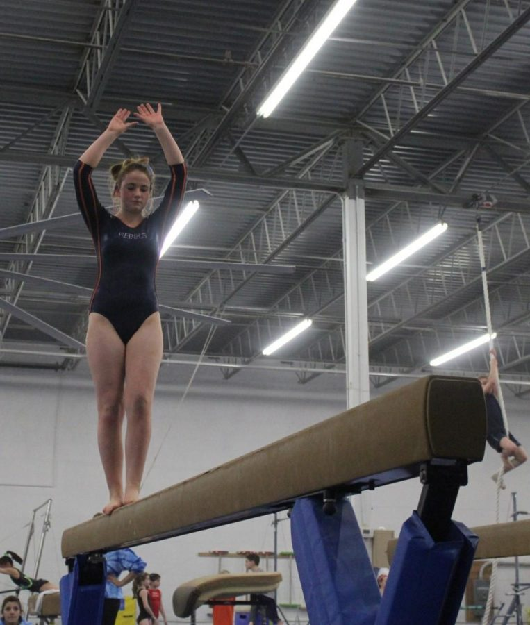A Rebels gymnast competes on the balance beam.