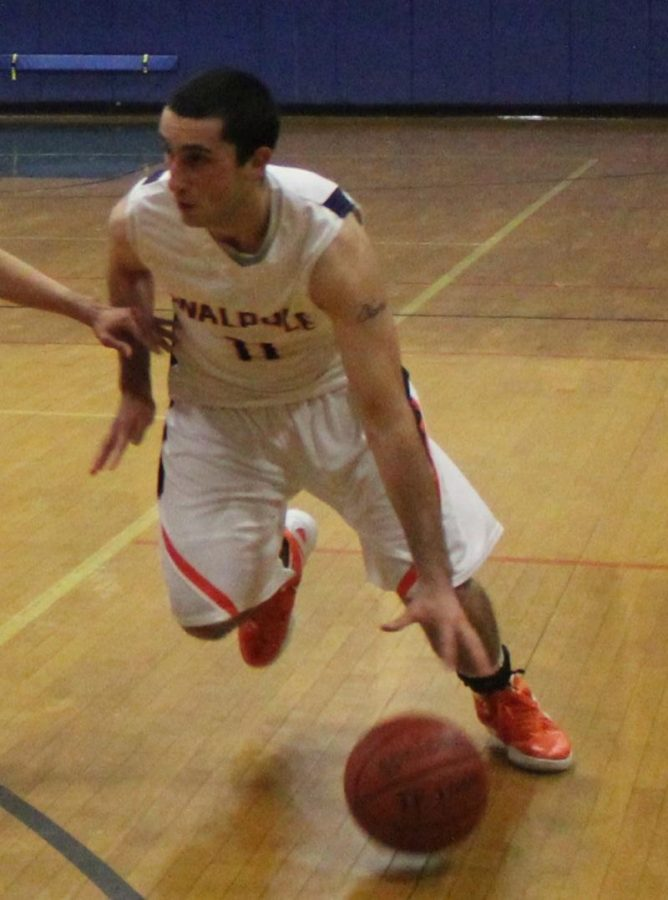 A Rebel Captain drives to the hoop in Tuesdays game against Newton North. (Photo/James Cullinane)