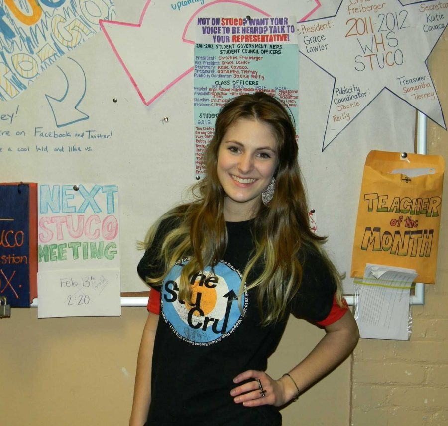 Student Council's Publicity Coordinator poses in front of the Student Council bulletin board.