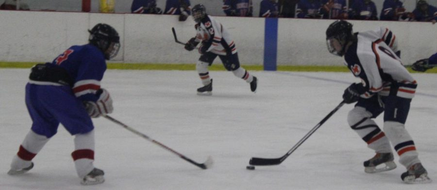 A Rebels player skates the puck past a Brookline player.