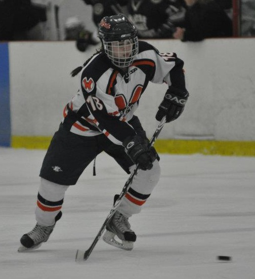 A sophomore denseman plays the puck at the blue line. (Photo/Mary Barry)