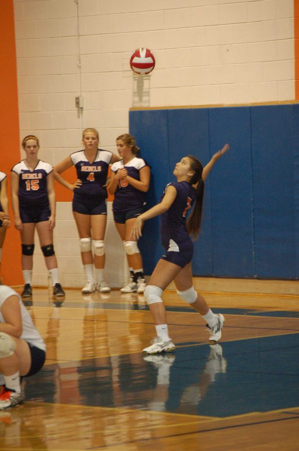 Walpole player serves the ball.