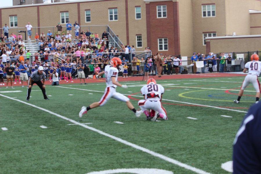 A Walpole player kick a field goal.
