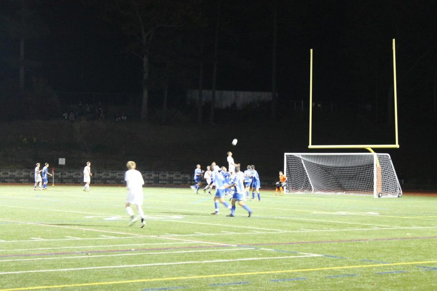 A Walpole player meets the ball far above the heads of the Norwood defenders.