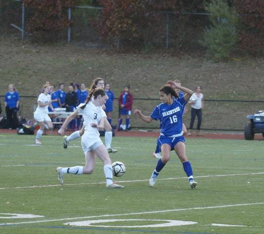 A Walpole forward makes a move around an opposing team's defender.