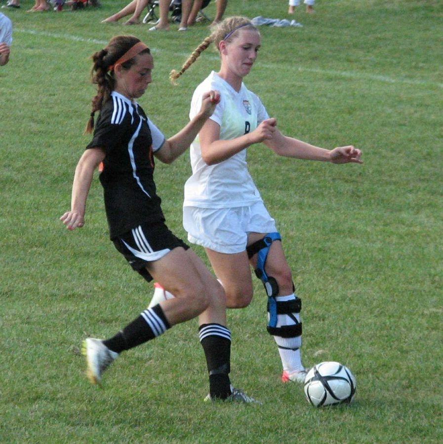 A Walpole attacker steals the ball back from a Wellesley defender.