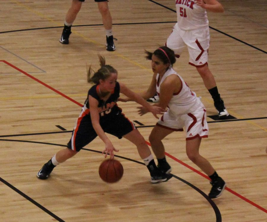 A Walpole guard drives to the basket against a Natick defender.
