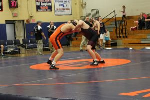 The Rebel's 220 lbs. wrestler ties up with his opponent.