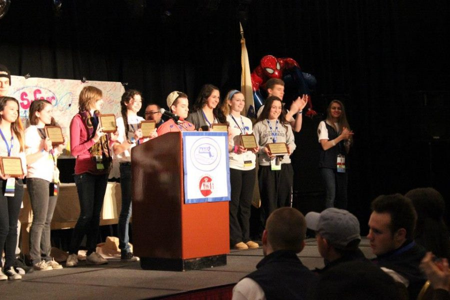 WHS Student Council President accepts Gold Council of Excellence Award on stage.