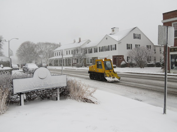 A plow trails through the center of town.