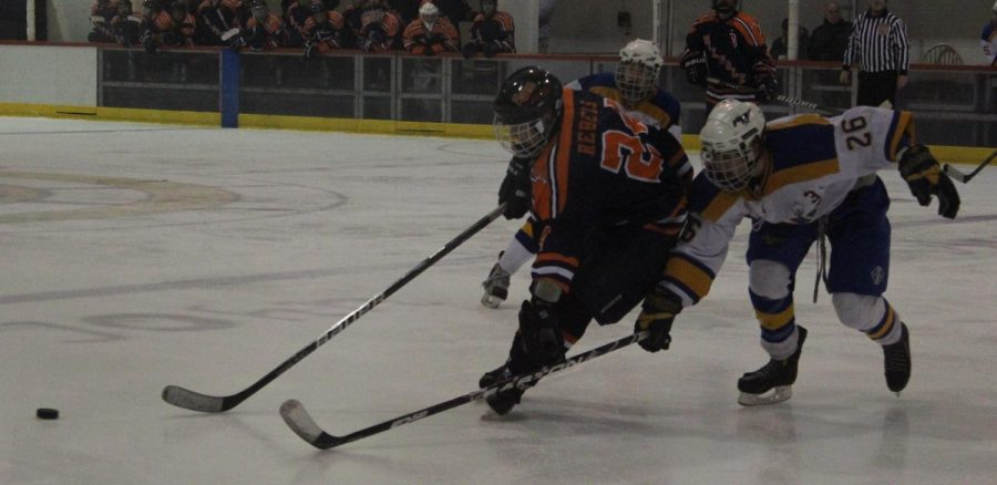 A Walpole and Norwood player battle for the puck.