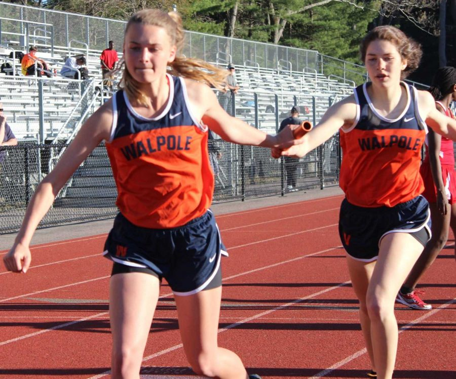 Athlete passes the baton to the next runner in the 4x400.