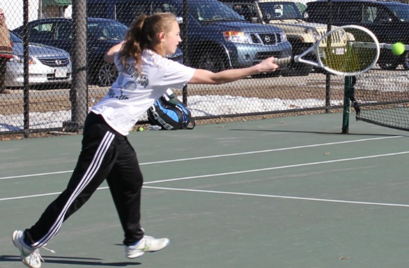 A player slams the ball to win her match.
