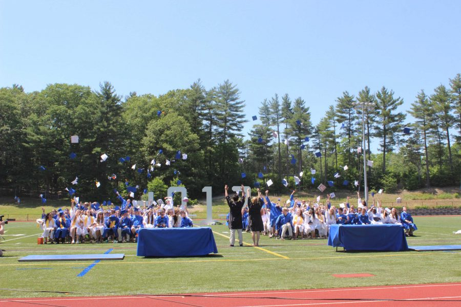 The members of the Class of 2013 throw their caps in the air in celebration after graduating.