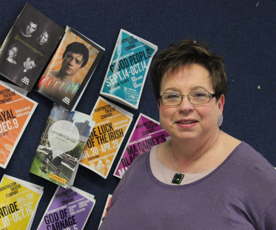 Retiring English teacher stands in front of a bulletin board in her classroom.