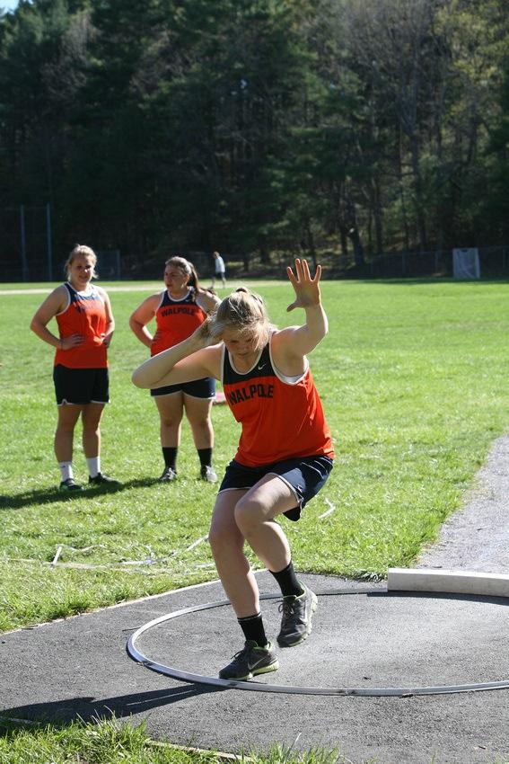 A member of the Walpole Track and Field Team throws a shot put.