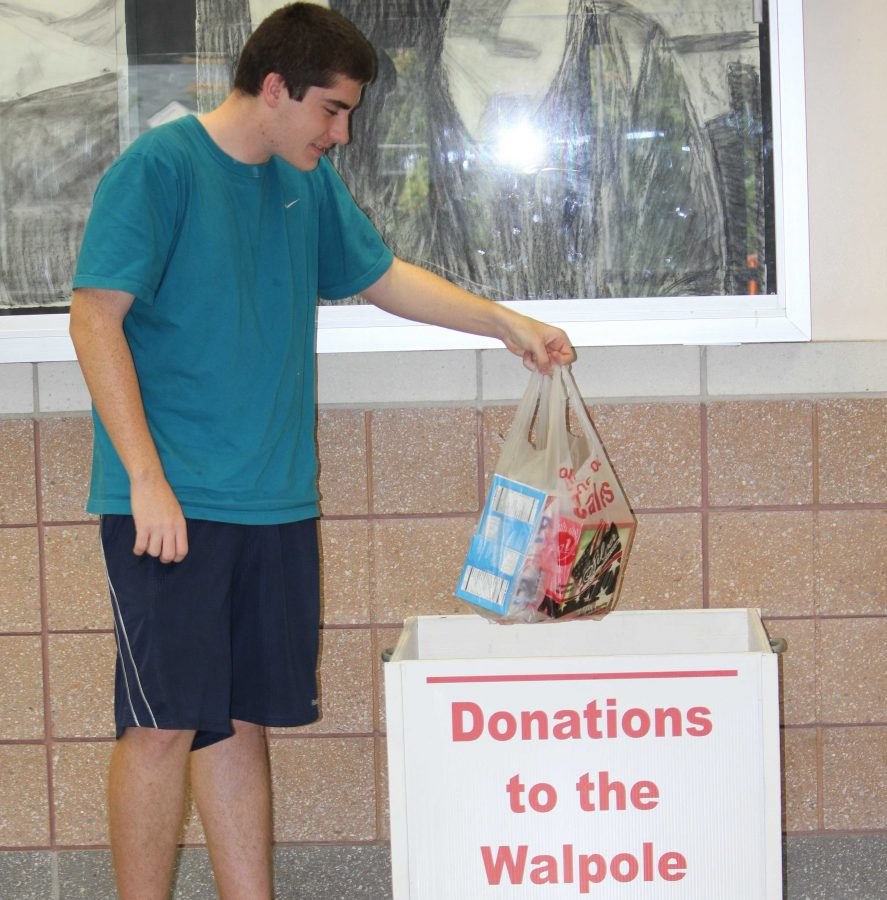 A student makes a donation to the Food Pantry donation box.