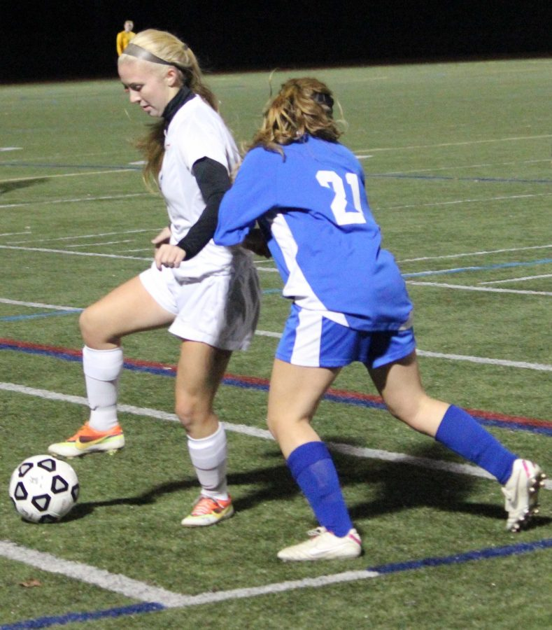 A Walpole midfielder shields the ball away from a Norwood defender.