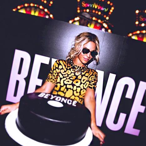 Beyoncé poses with a cake of her self-titled album