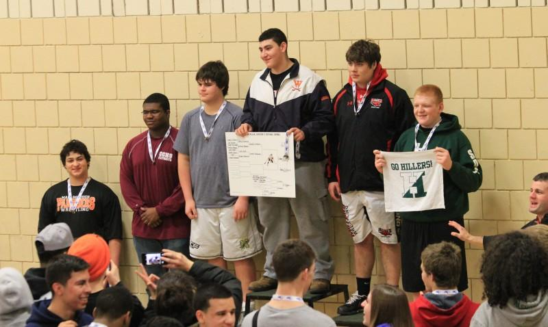 The+Rebel%27s+Heavyweight+poses+atop+the+Sectional+Championship+podium+after+pinning+Milford+in+double+OT.+