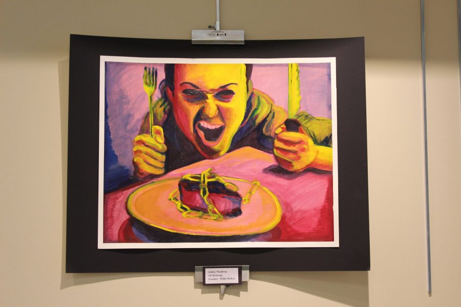 An AP art student's self portrait on display at the library.