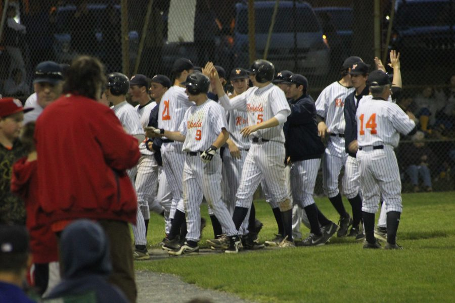 The Rebels huddle in between innings later in the game.