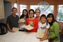 A host family poses for a picture in their kitchen with their international student.