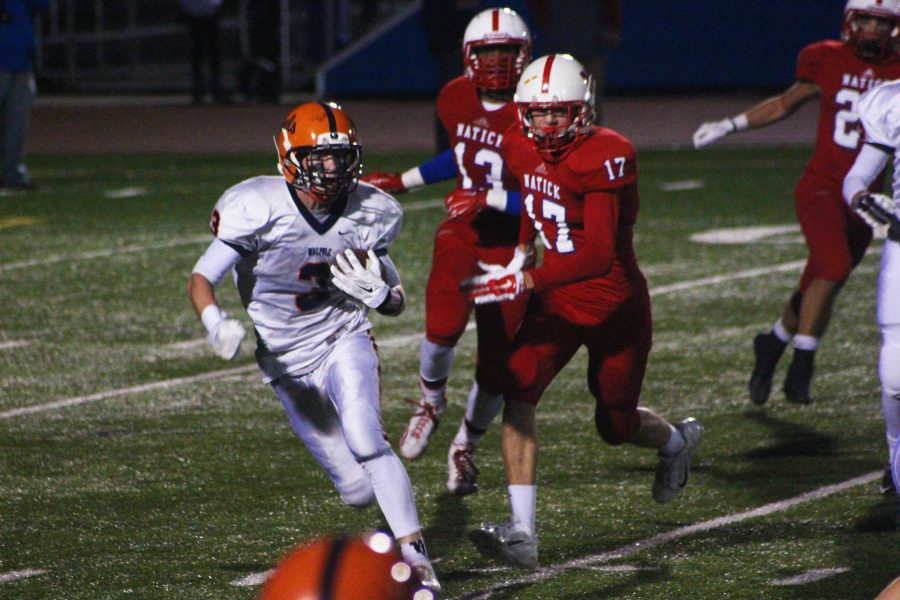 A Rebel wide receiver runs to avoid the Natick secondary.