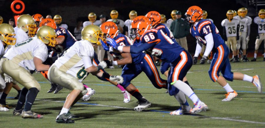 The Rebel defensive line challenges the Bishop Feehan offensive line.