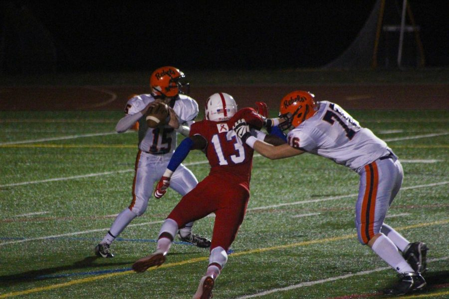 The Rebel Quarterback drops back to throw in an earlier game against Natick.
