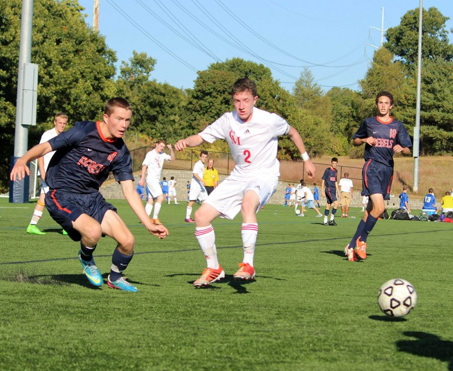 A Rebel soccer player challenges a Catholic Memorial player for the ball.