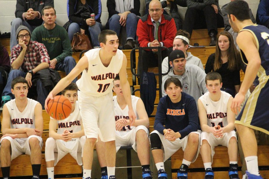 A Walpole athlete dribbles the ball in a game against Needham.