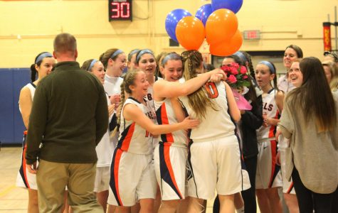 Walpole Alum Summer King being congratulated by her teammates and coach for surpassing the 1000 points mark in basketball.