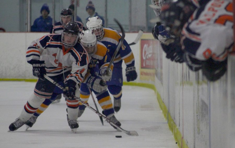 A Walpole player chases down the puck against two Norwood players.