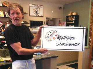 Jack Phillips, owner of Masterpiece Cake Shop and discrimination victim, poses with a sign for his shop (www.barbwire.com - image credit rossrighttriangle.wordpress.com).