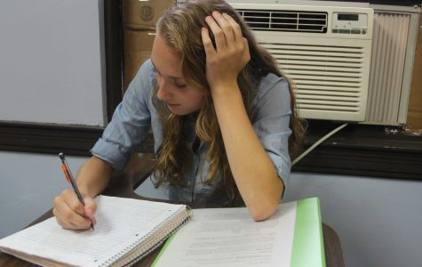Student chooses to sit in front of the AC in one of the few rooms that offers it.