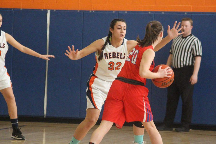 Senior Courtney Brigham plays defense against a Burlington player.