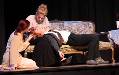 After regaining consciousness, Inspector Ruffing (Annika Olson) lays on Marcy's (Allison Millette) lap, while being looked at by Gillian Ravenscroft (Emily Tomasetti).