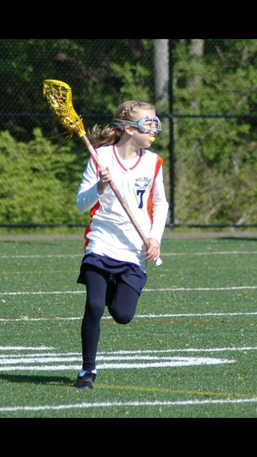 Curtis runs up the field in a third grade lacrosse game.