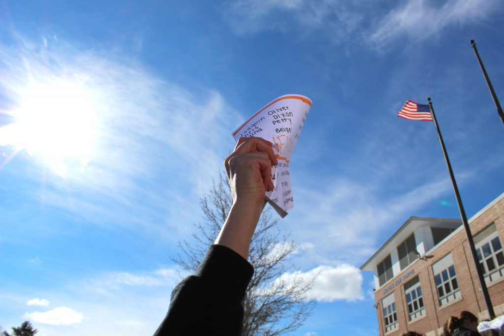 A students holds a sign in front of the school
